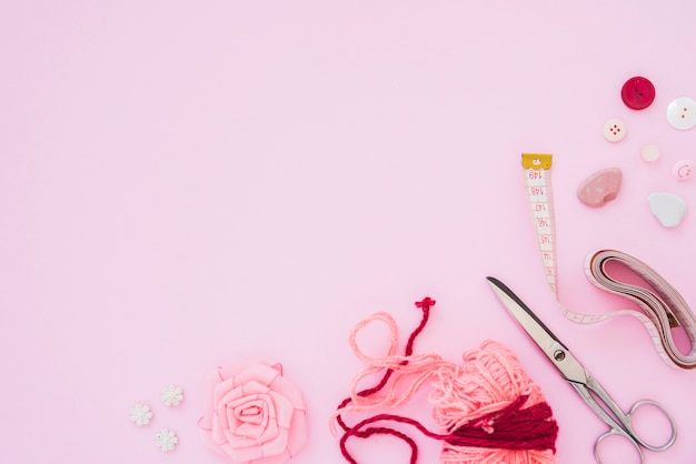 Rose ribbon; wool; scissor; measuring tape; and buttons on pink backdrop with copy space for writing the text
