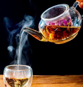유리 잔에 담긴 장미 찻잎은 주전자에서 뜨거운 물로 끓입니다. 나무 테이블과 검은 색 바탕에.