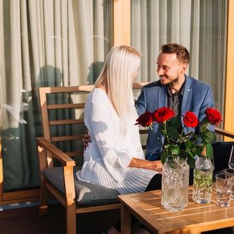 レストランで一緒に座ってロマンチックなカップルの前にローズの花瓶