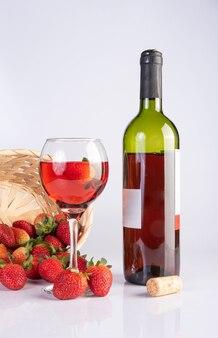 흰색 표면에 있는 아름다운 딸기와 함께 장미 와인 병과 크리스탈 유리, 선택적 초점.