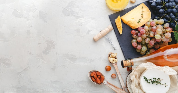로즈 와인 병 치즈 견과류와 분홍색과 검은색 포도, 꿀. 카망베르 치즈, 와인 바 스낵. 밝은 회색 소박한 콘크리트 배경에 와인 구성입니다. 복사 공간이 있는 긴 웹 배너입니다.