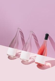 パステルパープルとピンクの背景にロゼワインボトル。夏のアルコール飲料のコンセプト。