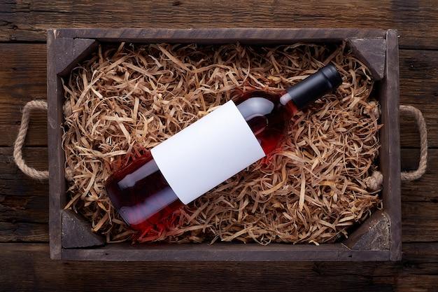 開いた木製の箱に詰められたロゼワインボトル