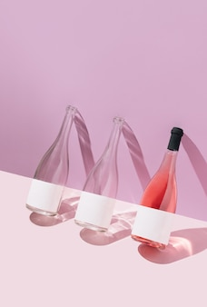Rose wine bottles on pastel purple and pink background. summer alcoholic drink concept.