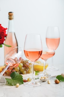 Rose wine in different glasses on gray concrete background minimal wine still life composition