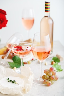 Rose wine in different wineglasses bottle on white table with grapes cheese, snacks bouquet of flowers. modern still life rose wine composition on light grey concrete background. vertical photo.