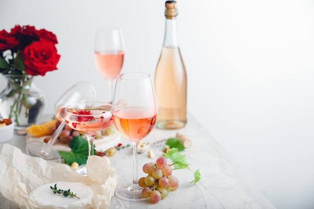 Rose wine in different wineglasses, bottle on white table with grapes cheese, snacks bouquet of flowers. modern still life rose wine composition on light grey concrete background with copy space.