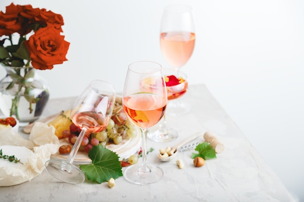 Rose wine in different wineglasses bottle on white table with grapes cheese, snacks bouquet of flowers. modern still life rose wine composition on light grey concrete background.