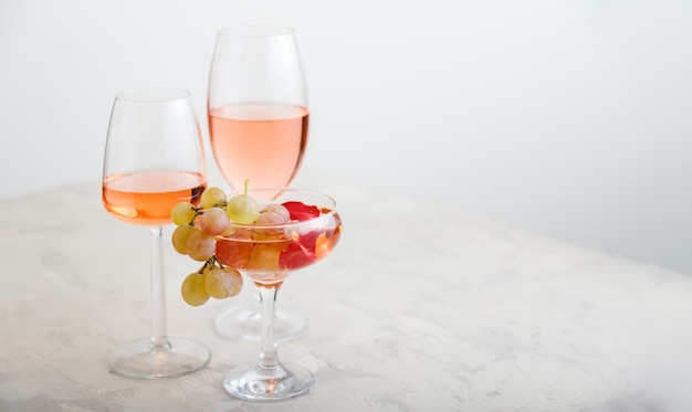 Rose wine in different wineglasses on white table with pink grapes modern still life wine