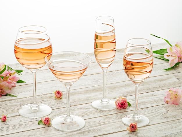 다른 안경에 로즈 와인. 흰색 나무 테이블에 5 개의 와인 잔입니다.