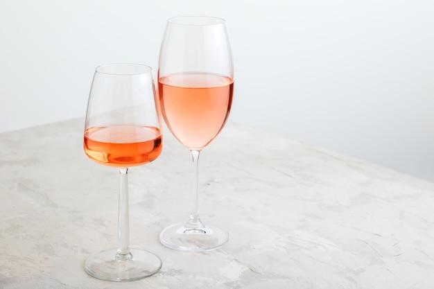 밝은 콘크리트 배경에 다양한 종류의 안경에 장미 와인. 복사 공간이 있는 흰색 테이블에 최소한의 와인 구성.