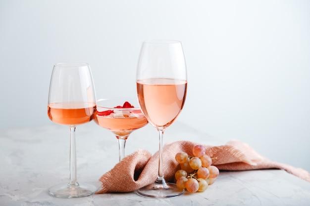 포도와 밝은 회색 콘크리트 배경에 안경의 다른 유형에 로즈 와인. 흰색 테이블에 로즈 와인 구성입니다.