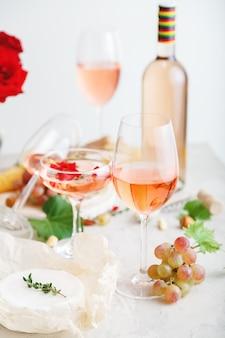 Розовое вино в бутылке различных бокалов на белом столе с виноградным сыром, закусками, букетом цветов. современный натюрморт состав розового вина на светло-сером фоне бетона. вертикальное фото.
