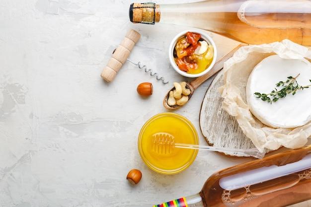 로즈 와인 핑크 샴페인 허니 브리 치즈 견과류 스낵 전채는 밝은 회색 돌 배경에 설정됩니다. 와인 파티 저녁 식사를 위한 지중해 음식 음료.