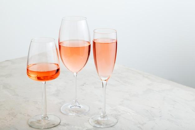 ワインテイスティングでロゼワインの夏の飲み物。灰色の背景にピンクのワインのグループグラス。コピースペースのあるロゼワイン品種のミニマルなレイアウト。