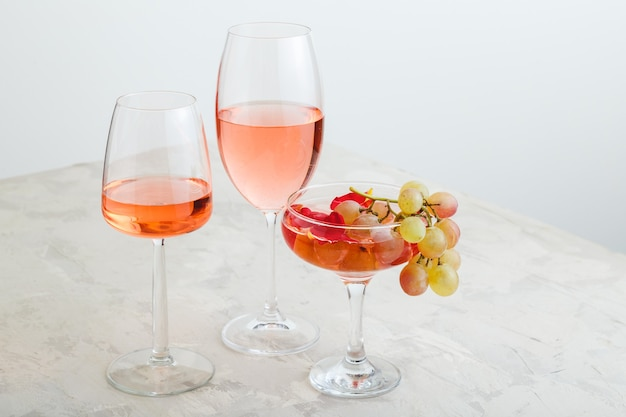 Rose wine and summer drinks champagne cocktail with grapes at wine tasting. group glasses of pink wine on gray background. rose wine variety minimal layout with copy space.
