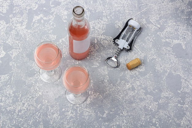 Rose wine tasting layout. opened bottle, two glasses and corkscrew with rose wine on a grey background.