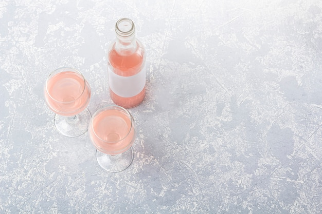Rose wine tasting layout. opened bottle and two glasses with rose wine on a grey background.