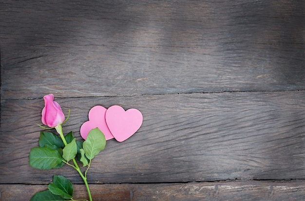 木製の背景にハートのカップルとバラ。暗い木製の背景にコピースペースとピンクのハートとピンクの花