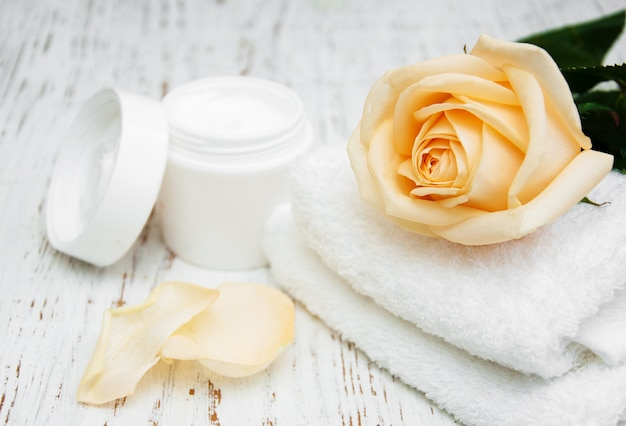 Rose with moisturiser cream and towels