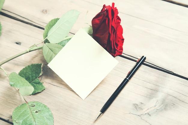 나무 테이블에 종이와 장미