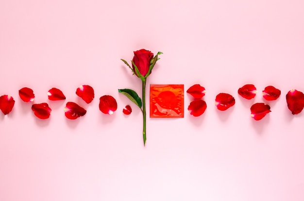 Rose with petals and condom package for minimal safe sex world sexual health and aids day concept