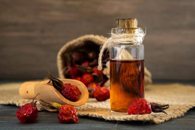 Масло шиповника на деревянных досках на темном фоне. флакон перевязан шнурком с эфирным маслом шиповника. мешок ягод.