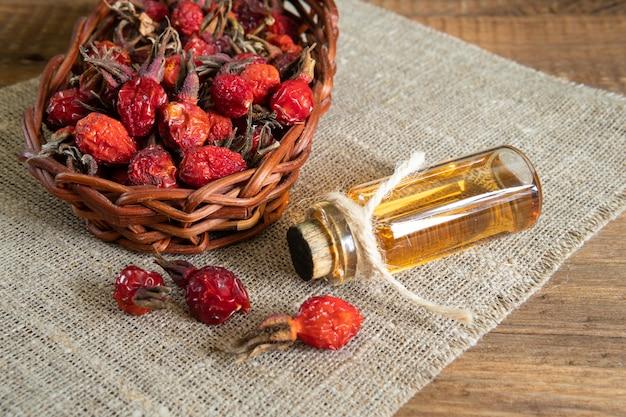Масло шиповника на деревянных досках на холсте с плодами шиповника
