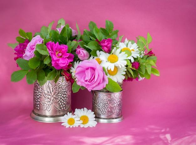 로즈힙 장미와 카모마일 꽃다발. 정원 꽃의 여름 꽃다발입니다. 분홍색 배경에 정