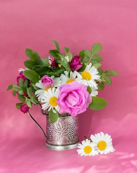 Rosehip rose and chamomile bouquet . summer bouquet of garden flowers. still life on the pink background