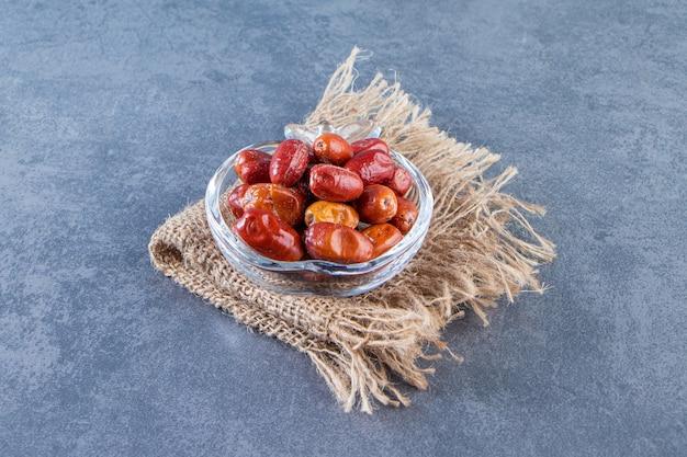 Плоды шиповника в стеклянной миске на текстуре на мраморной поверхности