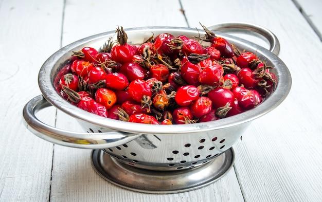 Плоды шиповника в металлической миске на деревянном столе