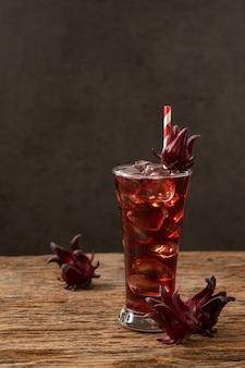 木製テーブルのアジアのレシピで新鮮なロゼルフルーツとローゼル透明なガラス