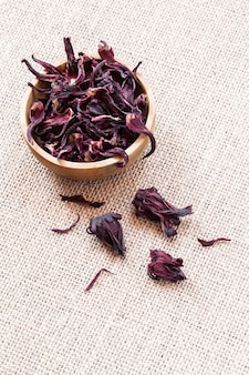 Сухие цветки гибискуса (roselle, karkade) в деревянном шаре на предпосылке мешковины с концом-вверх copyspace. здоровый органический витамин травяной чай.