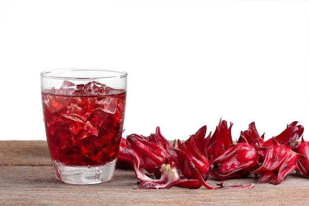 Безалкогольный напиток roselle с плодами roselle или гибискусом sabdariffa на деревянном, изолированном на белом