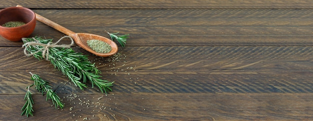 Rosemary bound on a wooden board with dried herbs and seeds.