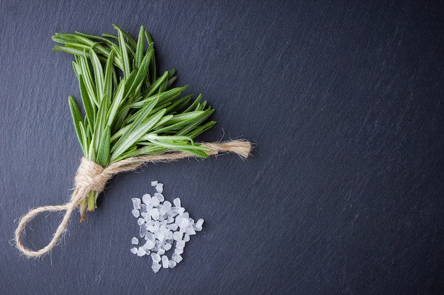 Rosemary bundle tied with twine on a black background. fresh rosemary and salt on slate stone. herbs for cooking meat dishes with copyspace. top view