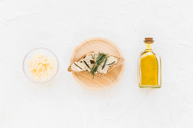 Rosemary and cheese on bread with oil bottle on white backdrop
