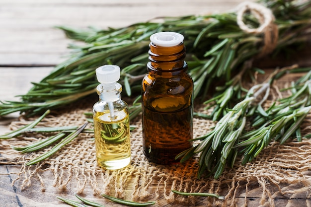 Rosemary essential oil in a glass bottle with fresh branch rosemary herb
