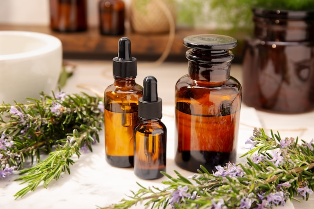 Rosemary essential oil on vintage apothecary bottles. herbal oil for skin care, aromatherapy and natural medicine