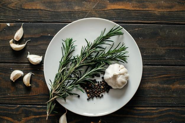 ローズマリー、ニンニク、コショウを皿に盛り付けます