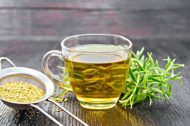 Rosemary herbal tea in a cup, a strainer with dry herb on a dark wooden board background