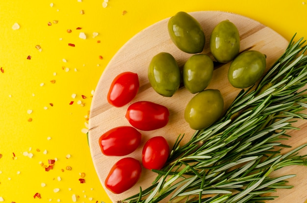 Rosemary herbs, olives and tomatoes cherry on wooden board on yellow background