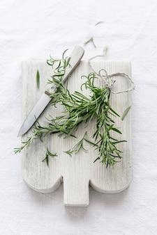 Rosemary leaves on cut board flat lay