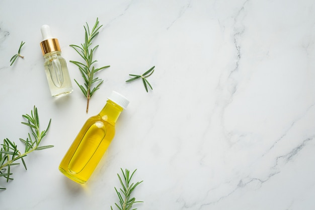 Rosemary oil in bottle with rosemary plants
