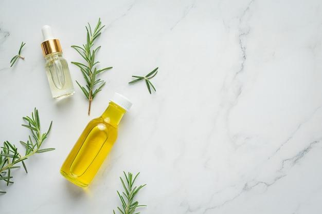 Масло розмарина в бутылке с растениями розмарина