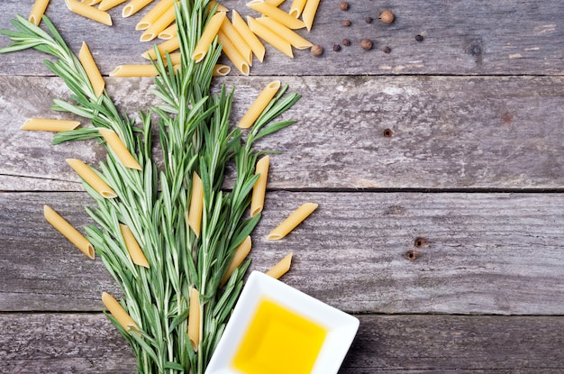 Rosemary, penne pasta, olive oil and peppers on the old wooden background