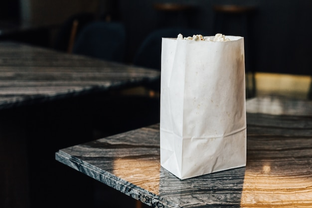 Rosemary popcorn in paper bag on top marble table on the left side