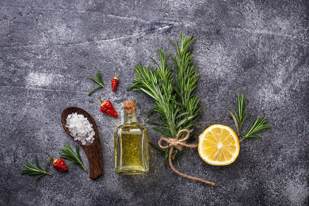 Rosemary, salt, lemon, oil and pepper. various spices on concrete background. top view