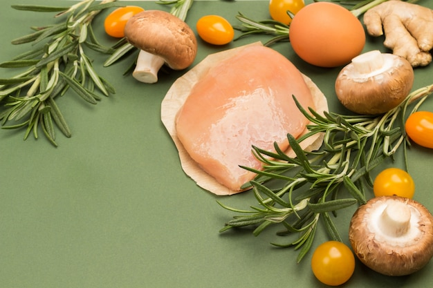 Rosemary sprigs, yellow tomatoes. chicken fillet on paper. green surface, top view, copy space